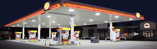 A picture of a gas station and c-store at night.