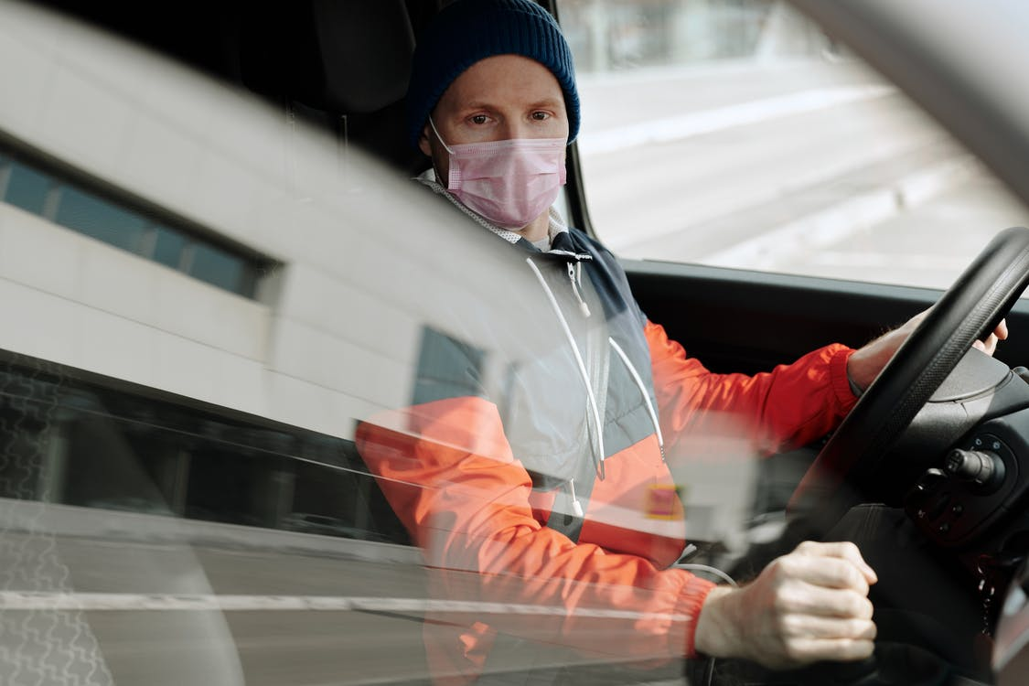 A man sitting in a vehicle with a mask